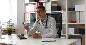 El doctor puso la botella de agua en la tabla almacen de metraje de vídeo