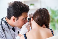 El doctor que comprueba el oído de los pacientes durante el examen médico fotografía de archivo libre de regalías