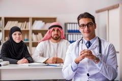 El doctor que consulta a la familia árabe en el hospital fotografía de archivo