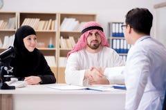 El doctor que consulta a la familia árabe en el hospital foto de archivo