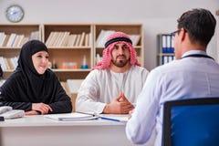 El doctor que consulta a la familia árabe en el hospital imagen de archivo libre de regalías