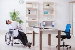 El doctor que descansa sobre la silla de ruedas en hospital después de turno de noche imagen de archivo libre de regalías
