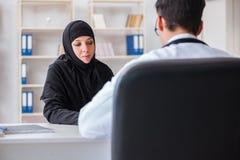 El doctor que visita de la mujer musulmán para el chequeo regular fotografía de archivo