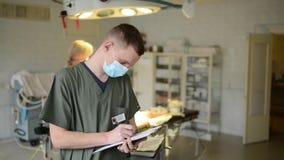 El doctor registra los resultados del tratamiento paciente almacen de video