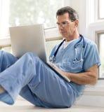 El doctor Reviewing Files en la computadora portátil foto de archivo