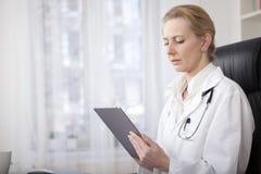 El doctor serio Holding de la mujer una tableta Fotografía de archivo