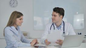 El doctor Sharing Good News con el paciente, llevando a cabo informe médico metrajes