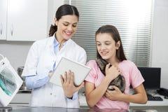 El doctor Showing Tablet Computer a la muchacha que sostiene la comadreja imágenes de archivo libres de regalías