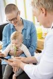 El doctor Showing Tablet Computer a la mujer con el bebé fotos de archivo