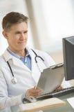 El doctor Smiling While Looking en el ordenador Imágenes de archivo libres de regalías