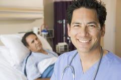 El doctor Smiling In Patients Room Imágenes de archivo libres de regalías