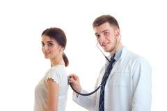 El doctor sonriente joven lindo escucha detrás estetoscopio de las muchachas aislado en un fondo blanco Imagen de archivo