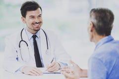 El doctor sonriente Talking con el paciente en su oficina Imagenes de archivo