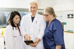 El doctor sonriente Using Digital Tablet con Team In Clinic foto de archivo libre de regalías