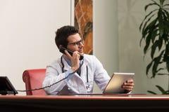 El doctor Talking On Telephone en oficina Fotografía de archivo libre de regalías