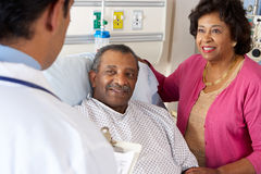 El doctor Talking To Senior Couple en sala fotografía de archivo