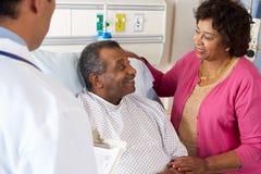 El doctor Talking To Senior Couple en sala Fotografía de archivo libre de regalías