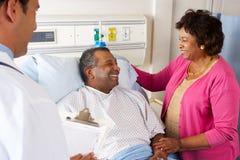 El doctor Talking To Senior Couple en sala fotos de archivo