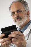 El doctor Texting en un teléfono celular Foto de archivo libre de regalías