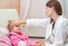 El doctor toca la frente una pequeña muchacha enferma Imagen de archivo libre de regalías