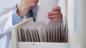 El doctor toma un documento médico del archivo y escribe la información almacen de metraje de vídeo
