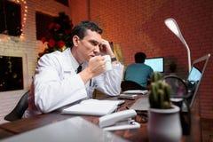 El doctor trabaja en el ` s Eve del Año Nuevo Él bebe cansadamente el café Detrás de él trabajos un colega Imagen de archivo