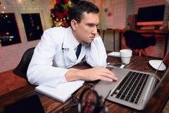 El doctor trabaja en el ` s Eve del Año Nuevo Él está muy cansado pero continúa trabajando Foto de archivo libre de regalías