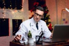 El doctor trabaja en el ` s Eve del Año Nuevo Él está muy cansado pero continúa trabajando Imagen de archivo libre de regalías