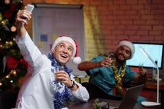 El doctor trabaja en el ` s Eve del Año Nuevo Él puso el casquillo del ` s del Año Nuevo, sostiene un vidrio de whisky y hace un  Imagenes de archivo