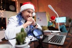 El doctor trabaja en el ` s Eve del Año Nuevo Él puso un sombrero del ` s del Año Nuevo y habla en el vídeo Fotografía de archivo libre de regalías