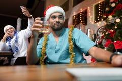 El doctor trabaja en el ` s Eve del Año Nuevo Él sostiene un vidrio de whisky y mira el monitor Imagenes de archivo
