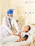 El doctor trata al paciente con el estetoscopio. Fotografía de archivo