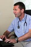 El doctor Typing On A Computer Imagen de archivo