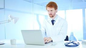 El doctor Typing en el ordenador portátil en hospital, pelirrojo imágenes de archivo libres de regalías
