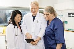 El doctor Using Digital Tablet con Team In Clinic imágenes de archivo libres de regalías