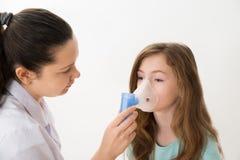 El doctor Using Inhaler Mask en muchacha Imágenes de archivo libres de regalías