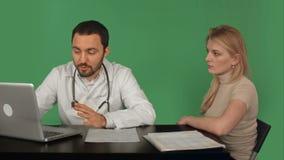 El doctor Using Laptop Discussing con el paciente en a almacen de metraje de vídeo