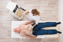 El doctor Using Ultrasound Scan en el abdomen del paciente masculino mayor Fotos de archivo