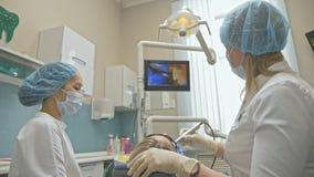 El doctor utilizó la cámara micro de Digitaces del control intraoral dental especial a los dientes del examen En monitor el denti almacen de video