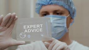 El doctor utiliza la tableta con asesoramiento de experto del texto almacen de metraje de vídeo