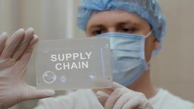 El doctor utiliza la tableta con la cadena de suministro del texto almacen de video
