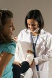 El doctor venda a una muchacha pie-Vertical Imagen de archivo
