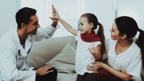 El doctor Visiting Little Girl en bufanda roja con frío imagen de archivo
