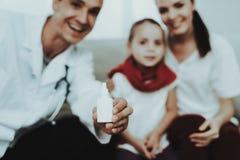 El doctor Visiting Little Girl en bufanda roja con frío imagenes de archivo