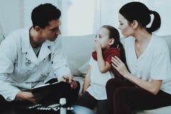 El doctor Visiting Little Girl en bufanda roja con frío fotografía de archivo libre de regalías