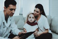 El doctor Visiting Little Girl en bufanda roja con frío fotografía de archivo