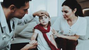 El doctor Visiting Little Girl en bufanda roja con frío imagen de archivo libre de regalías