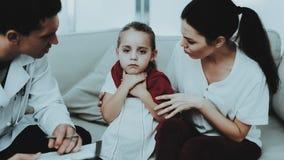 El doctor Visiting Little Girl en bufanda roja con frío foto de archivo