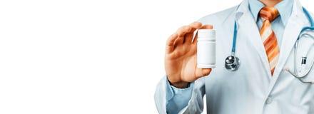 El doctor In White Coat con un estetoscopio en el hombro que sostiene una botella de píldoras entre sus fingeres Estafa médica de Fotos de archivo