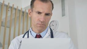 El doctor Working en la computadora portátil almacen de video